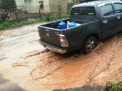 Một chiếc ô tô lưu thông tại đoạn đường qua thôn Hàm Rồng trong tình trạng vượt hố bom trên đường